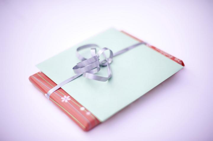 a christmas present and greetings card bundled with a ribbon and bow