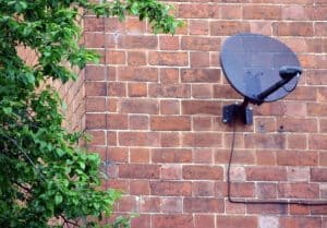 A picture of a satellite dish attached to a red brick wall